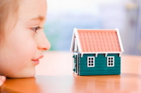 Child looking at a small home